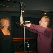 Engineer Chris Brooke adjusts Carole's microphone. Photo by Rudy Guess